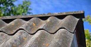 Céu azul sobre as telhas de telhado velhas do asbesto perigoso imagens de stock royalty free