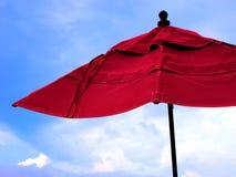 Céu azul vermelho de guarda-chuva de praia Foto de Stock