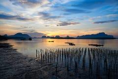 Céu bonito na manhã e um pescador no barco do longtail imagens de stock royalty free