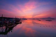 Céu bonito na vila do fsherman durante o nascer do sol e os barcos do longtail do pescador imagem de stock royalty free