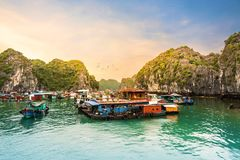 Céu colorido com a mosca do pássaro na vila de flutuação no mar abaixo dos penhascos da pedra calcária da baía de Halong, Vietnam imagens de stock
