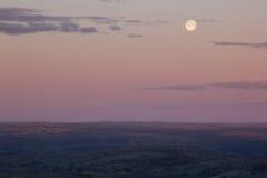 Céu cor-de-rosa macio do por do sol sobre o vale da montanha com Lua cheia Foto de Stock