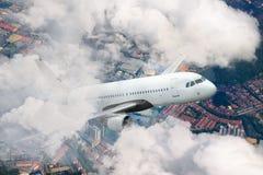 Céu de voo plano Avião acima da cidade Escaladas brancas dos aviões de passageiro através das nuvens imagens de stock royalty free