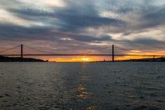 Céu do por do sol acima de Tagus River, de ponte o 25 de abril Lisboa e de porto do navio, Portugal Fotografia de Stock Royalty Free