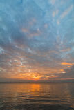 Céu do por do sol com nuvens alaranjadas e o barco distante imagens de stock