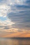 Céu do por do sol com nuvens alaranjadas e o barco distante imagem de stock royalty free