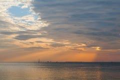 Céu do por do sol com nuvens alaranjadas e o barco distante foto de stock