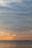 Céu do por do sol com nuvens alaranjadas e o barco distante fotos de stock royalty free