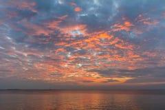 Céu do por do sol com nuvens alaranjadas e o barco distante fotografia de stock