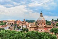 Céu dramático do por do sol acima da igreja de Santi Luca e Martina e grande Roman Colosseum Fotografia de Stock