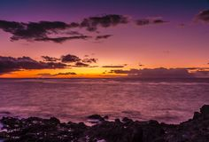 Céu e oceano azuis, roxos e alaranjados do por do sol imagens de stock