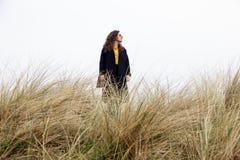 Céu encaracolado da grama seca da praia da costa do humor do cabelo longo do revestimento da mola da mulher do retrato do vento d fotos de stock royalty free