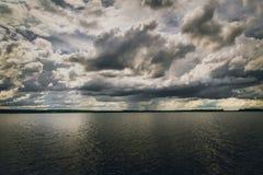 Céu escuro e detalhado acima da água imagem de stock