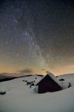 Céu estrelado acima das cabanas abandonadas nas montanhas Foto de Stock