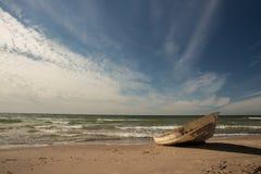 Céu impressionante sobre um barco de pesca na praia Báltico em Ventspils Foto de Stock Royalty Free