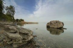 céu Leitoso-nebuloso sobre o lago Ohrid com duas rochas que olham como criaturas fabulosas Paisagem imagem de stock