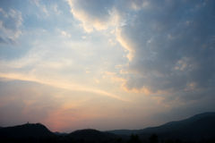 Céu nebuloso com montanha da silhueta Fotografia de Stock