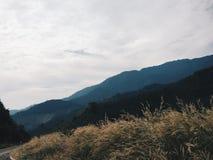 Céu nebuloso com silhueta das montanhas Foto de Stock