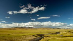 Céu nebuloso e rio das montanhas enormes do prado filme