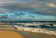 Céu nebuloso, sol e ondas Imagens de Stock Royalty Free