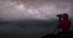 Céu noturno colorido do panorama com estrelas e silhueta de um homem ereto na pedra Via L?tea azul com o homem na montanha imagem de stock