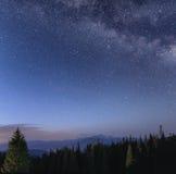 Céu noturno com Via Látea sobre a paisagem da montanha Fotos de Stock