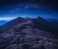 Céu noturno estrelado acima do cume da montanha Fotografia de Stock