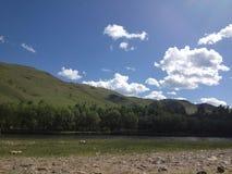 Céu, nuvens, árvores, montagens, rio Fotografia de Stock Royalty Free