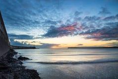 Céu vibrante bonito do nascer do sol sobre o oceano calmo da água com lightho Imagens de Stock Royalty Free