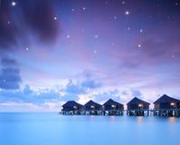 Céus estrelados sobre casas de campo da casa de campo da água na ilha de Kuredu, Mald imagens de stock royalty free