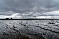 Céus tormentosos que fabricam cerveja sobre um lago em Staffordshire, Inglaterra imagem de stock royalty free