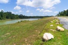 Cênico com linha da rocha na grama ao lado do rio e da estrada Imagem de Stock Royalty Free