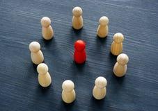 Círculo das figuras de madeira e da figura vermelha Discriminação ou perseguição fotografia de stock royalty free