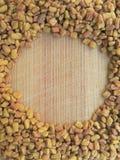 Círculo de la alholva en fondo de madera Imagenes de archivo