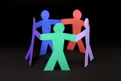 Círculo de la gente de papel colorida en fondo negro Fotos de archivo