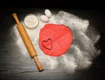 Círculo de la pasta roja con el recorte de la corazón-forma Tabla negra asperjada con la harina, el rodillo y los huevos Imágenes de archivo libres de regalías