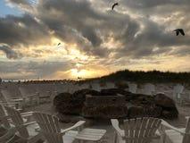 Círculo del fuego de la playa con las nubes y las gaviotas Fotos de archivo libres de regalías