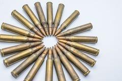 círculo dos cartuchos velhos 5 do rifle 56 milímetros em um fundo branco Foto de Stock Royalty Free
