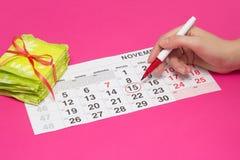 Círculo femenino de la mano los días en el calendario con un rotulador cuando ella tiene su período, fondo rosado, una pila de co fotos de archivo libres de regalías