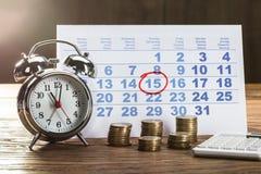 Círculo marcado no calendário com pulso de disparo e nas moedas na mesa fotos de stock