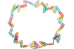 Círculo salvaje de clips de papel coloreados en el fondo blanco foto de archivo libre de regalías