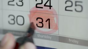 Círculo y pintura de la mano de la mujer durante día en calendario del papel 31ro día del mes almacen de metraje de vídeo