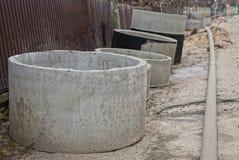 Círculos e anéis concretos perto de uma cerca no reparo da rua imagem de stock