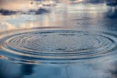 Círculos y reflexión del cielo en la superficie del agua de un lago Foto de archivo