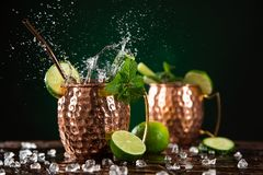 Cóctel alcohólico famoso de la mula de Moscú que salpica en las tazas de cobre foto de archivo libre de regalías
