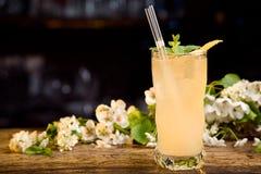 Cóctel amarillo del verano adornado con la corteza de la menta y de limón en una tabla de madera en un fondo floral Fotografía de archivo