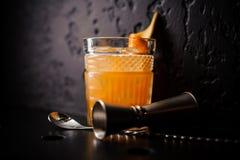 Cóctel anaranjado en cristal con la cuchara y el aparejo de la barra Fotografía de archivo libre de regalías