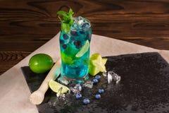 Cóctel azul de restauración brillante de la laguna con la cal, la menta, el hielo, los arándanos y el carambola en la tabla-servi Foto de archivo libre de regalías
