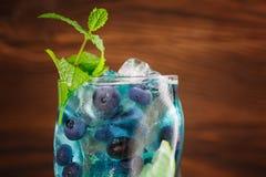 Cóctel azul de restauración colorido de la laguna con la menta, rebanada de la cal, cubos de hielo, arándanos en el fondo de made Fotografía de archivo