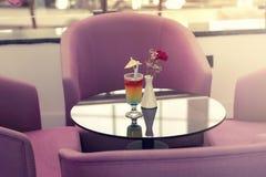 Cóctel brillante con el paraguas en la tabla rodeada por armchai fotografía de archivo libre de regalías